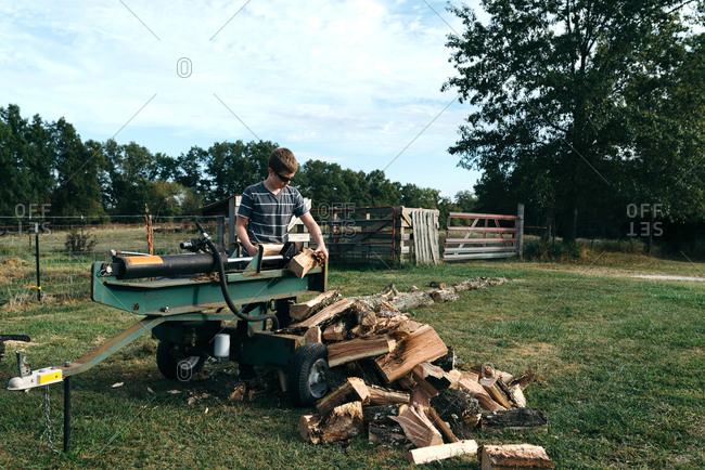 Teenage boy using a log splitter to chop firewood