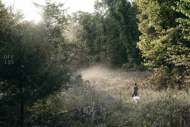 Teenage boy walking with dog in a forest