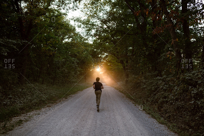 Teenage boy running down a dirt road at sunset