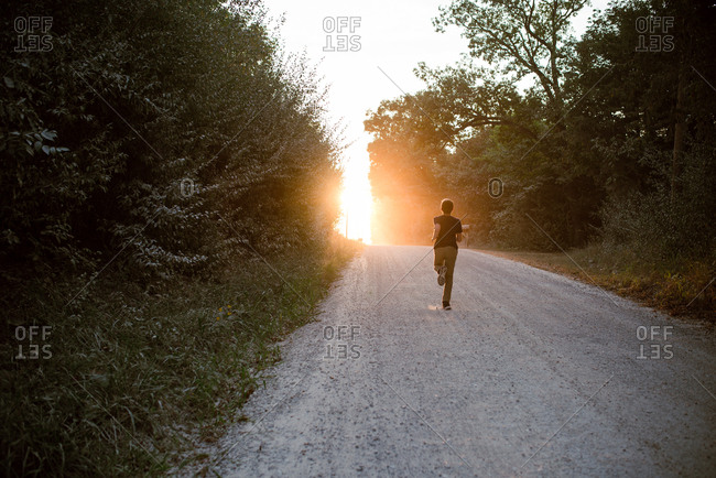 Boy running down a dirt road at sunset