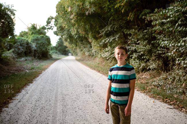 Teenage boy standing on a gravel road