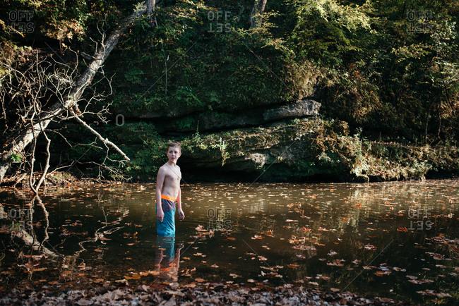 Boy walking in river with fallen leaves