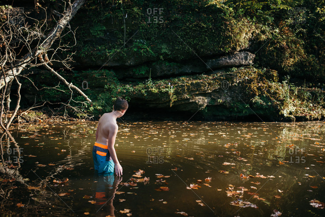 Boy swimming in river in autumn