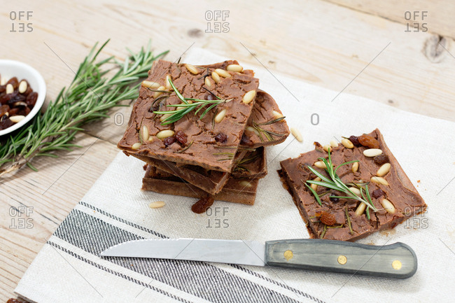 Tuscany cake Castagnaccio sliced on wooden table with rosemary and peanuts