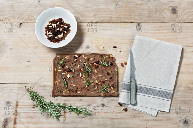 Tuscany cake Castagnaccio on wooden table with rosemary and peanuts