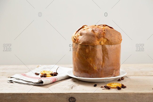 Italian Christmas cake panettone on wooden table with oranges and dried fruit