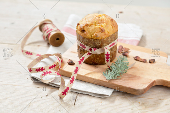 Italian Christmas cake panettone on wooden table being wrapped
