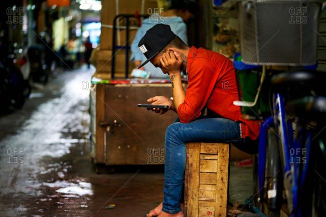Chinatown, Bangkok, Thailand - September 29, 2017: Man in a red shirt looking at his phone