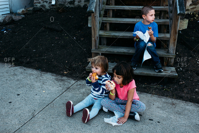 Kids sitting on a sidewalk eating donuts