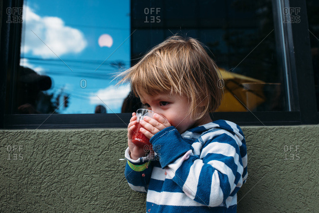 Toddler wearing stripes drinking red juice from a cup
