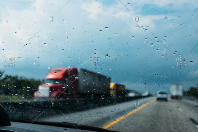 Out of focus view out windshield on a rainy highway