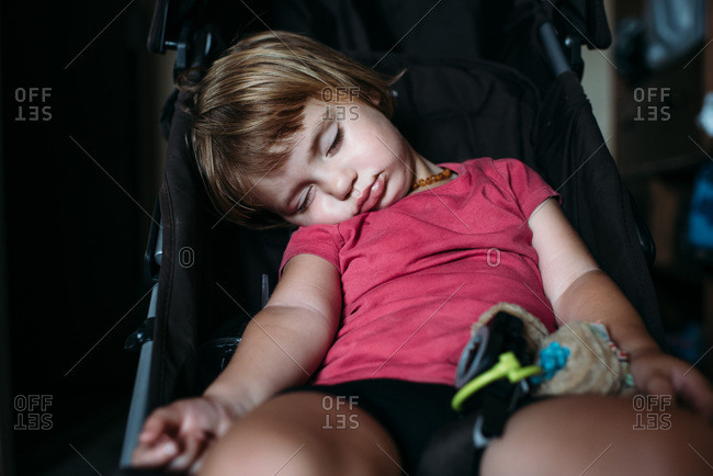 Toddler sleeping slumped over in a stroller