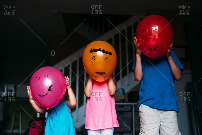 Children holding balloons in front of their faces with cartoon faces drawn on