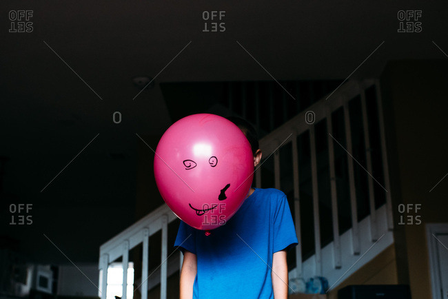 Child holding balloon in front of face with face drawn on it