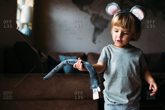 Toddler wearing grey mouse costume with tail fallen off