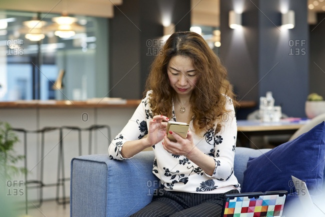 Woman in office looking at her phone