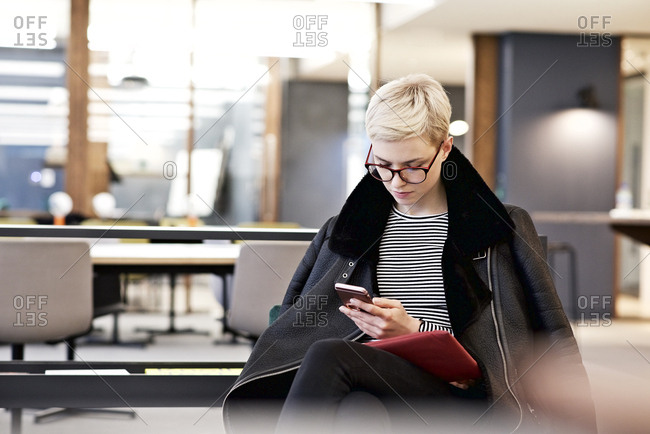 Woman in office checking phone in coat