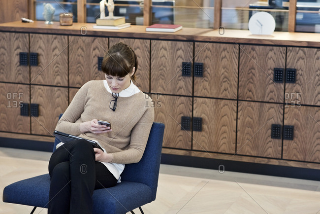 Woman in office with multiple devices