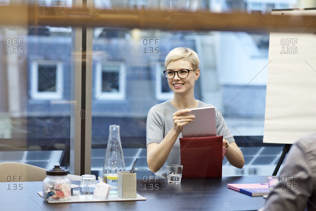Woman in office putting tablet in case