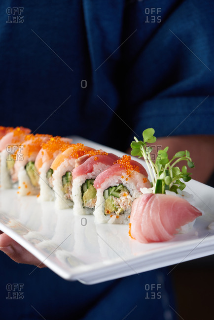 Japanese sushi chef holding a plated rainbow roll with crab and cucumber on the inside and topped with salmon, tuna, and yellowtail and finished with flying fish eggs and radish sprouts