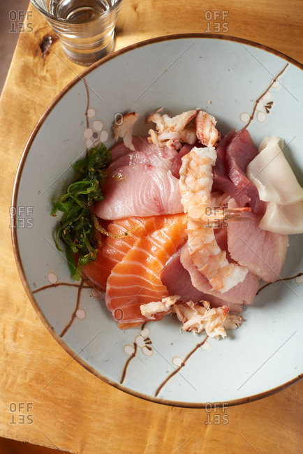 A bowl of Chirashi (scattered sashimi on rice) including raw cuts of salmon, yellowtail, tuna and shrimp served with a small bit of seaweed salad