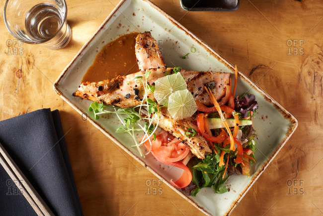 Two pieces of grilled salmon teriyaki over a light asian salad presented on a square plate with a glass of sake nearby