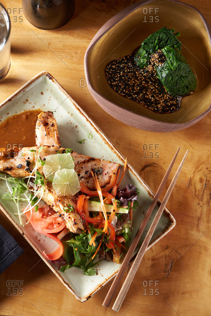 Two Japanese appetizer dish, a salmon teriyaki salad featuring two grilled pieces of salmon and a traditional spinach salad called Spinach Goma-ae both served with a glass of sake nearby.