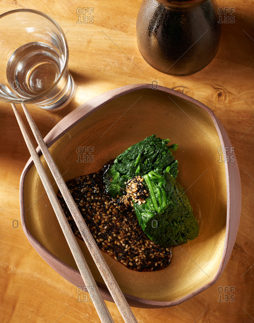 Traditonal Japanese appetizer salad of boiled spinach served with sesame seeds and a dark soy sauce in a gold container