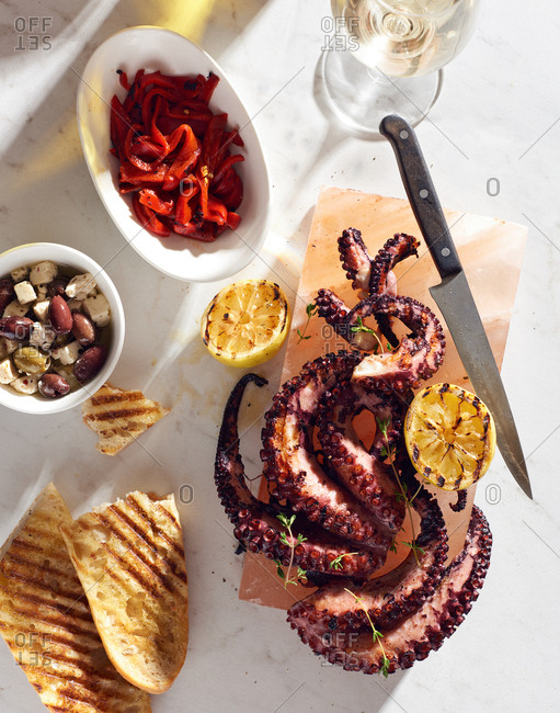 Mediterranean style grilled octopus served on a himilayan salt block with grilled lemon and grilled bread, with marinated feta and roasted red pepper and a glass of white wine on a white marble surface