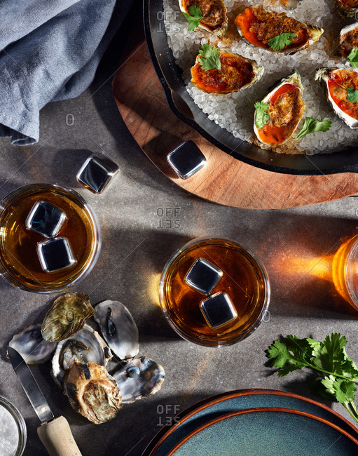 Whiskey presented with whiskey stones to chill the beverage and served with baked oysters in a cast iron skillet with a chipotle lime butter on a stone surface