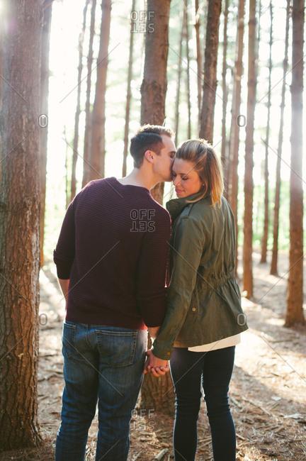 Man kissing woman's cheek in woods