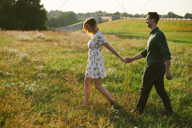 Happy couple strolling in field
