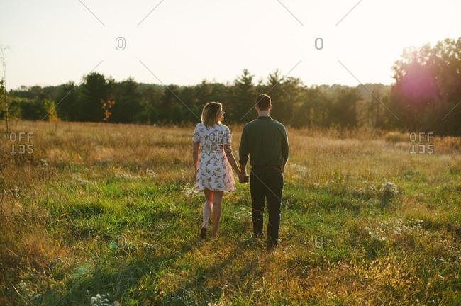 Happy couple strolling in a field
