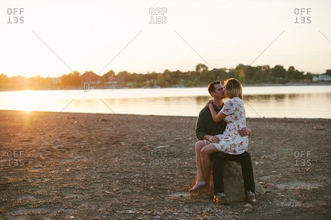 Woman kissing man on lake shore