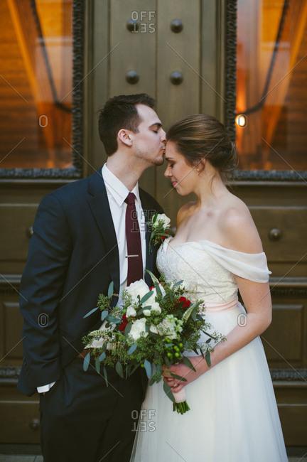 Groom kissing bride's forehead