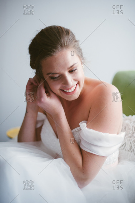 Smiling bride putting on earring