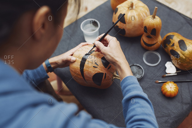 Woman painting pumpkins for Halloween