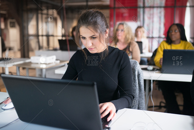 Young fashion design student working on a laptop computer