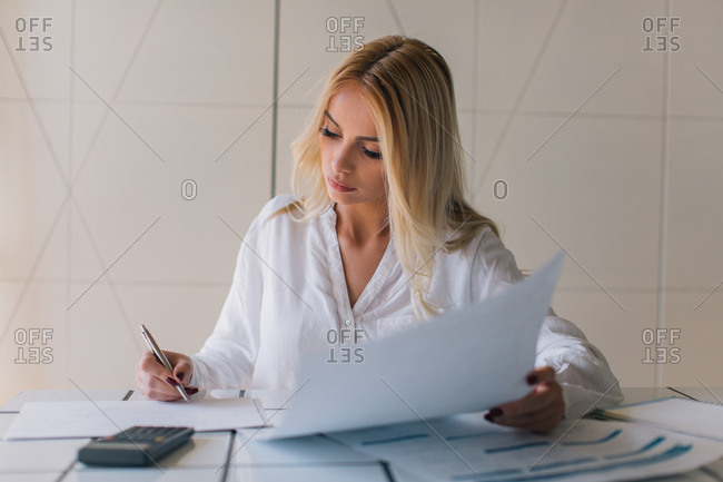 Young businesswoman holding paper and pen