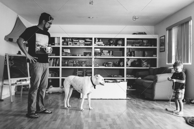 Father and son in living room with dog