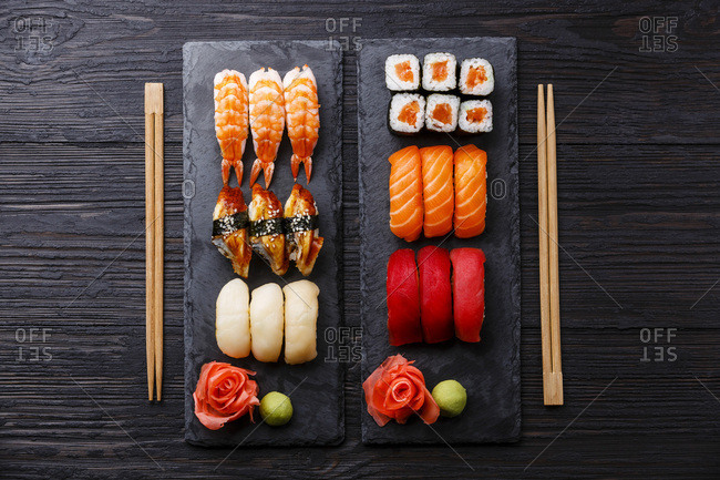 Sushi rolls, maki, nigiri Set served for two on black stone slate on dark wooden background