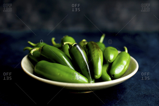 A Ceramic Bowl full of Jalapeno Peppers.  Photographed on a dark blue surface with a black/grey background.