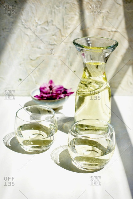 White wine served in a carafe.  Photographed on a white plaster background with an Italian plaster wall.