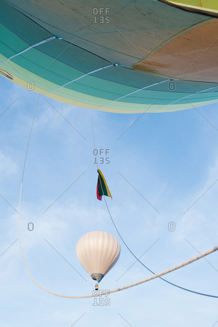 Shot of white aerostat taken from another air balloon on background of blue sky