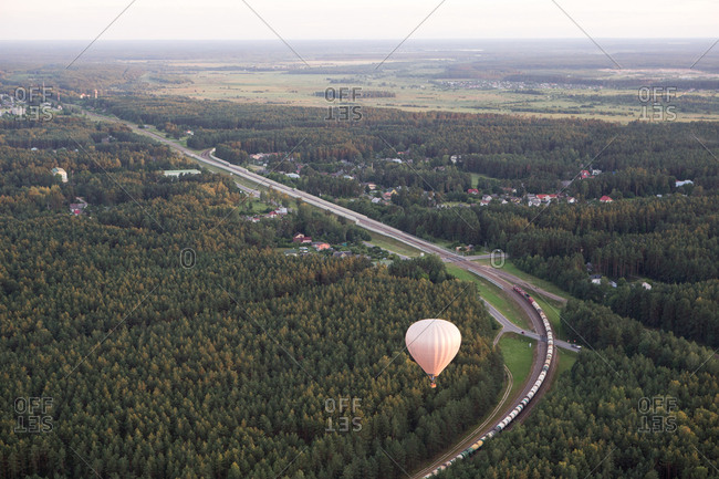 Aerial shot of white aerostat flying above green woods and highway