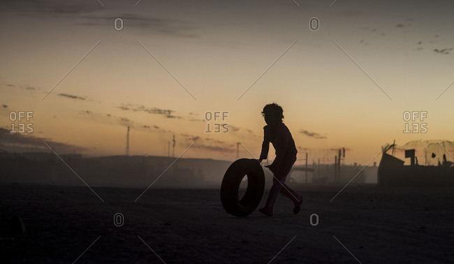 Silhouette of a poor child playing with the title abandoned tire