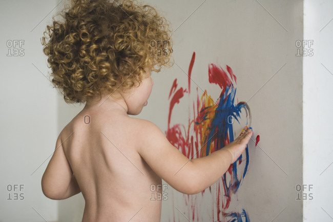 Back view of a child drawing abstract blots with hand on the wall