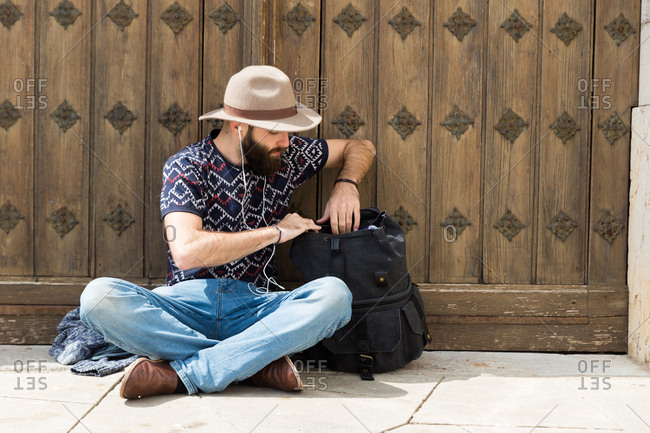 Horizontal outdoors shot of a man sitting on the ground and searching in a backpack while listening to music