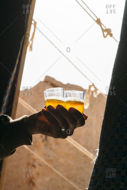 Hand of a person holding two glasses with the traditional beverage with foam