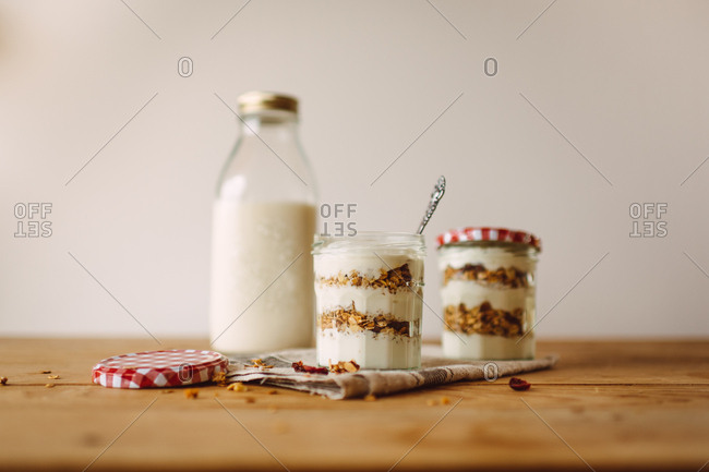 Two jars of muesli with yogurt next to a bottle of milk on a wooden table
